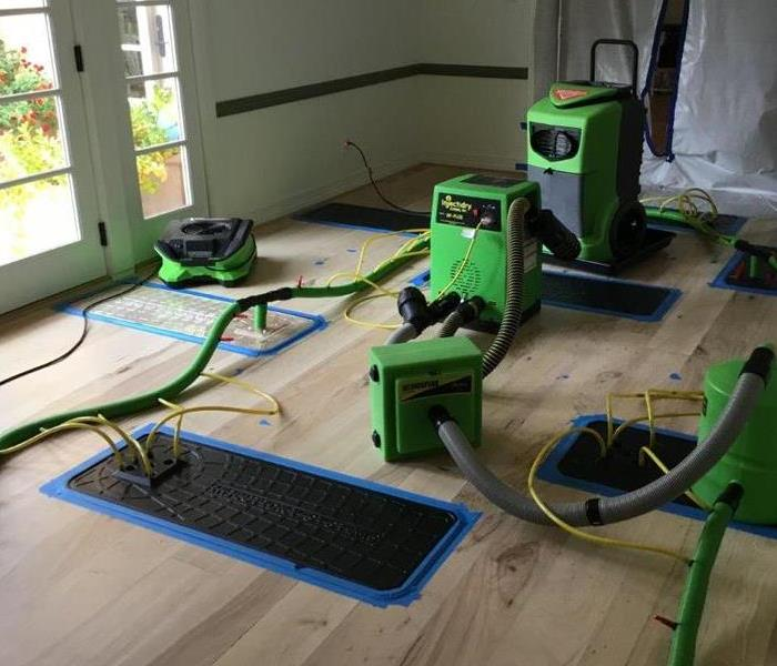 Wood floors covered in green air movers and black floor mats.