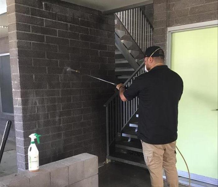 A SERVPRO technician is shown finishing graffiti removal from a wall