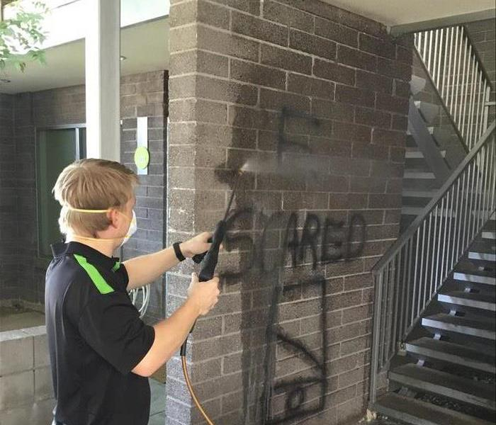 A SERVPRO technician is shown applying cleaning solution to graffiti on a wall