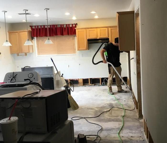 Empty kitchen with SERVPRO worker using a water extractor.