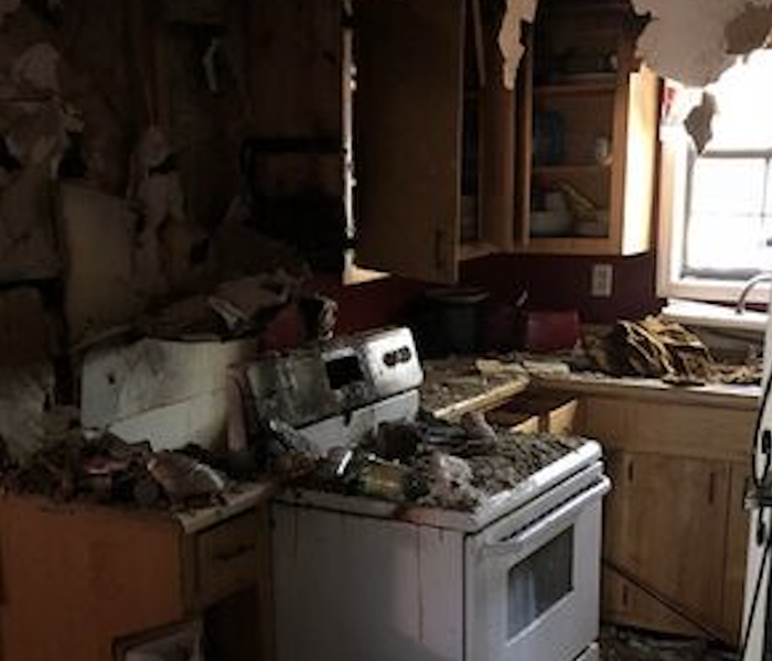 Kitchen with debris and soot.
