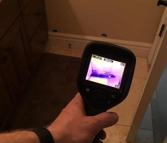 Moisture meter with a pink and purple screen.