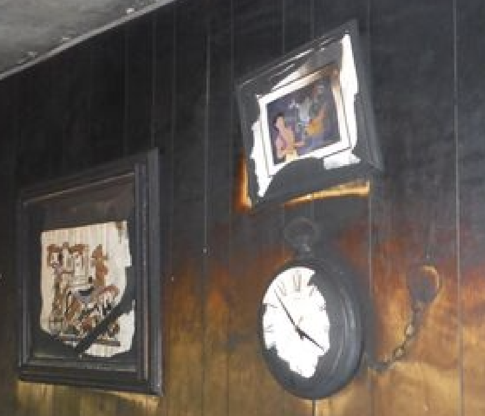 Black wall and burned pictures.