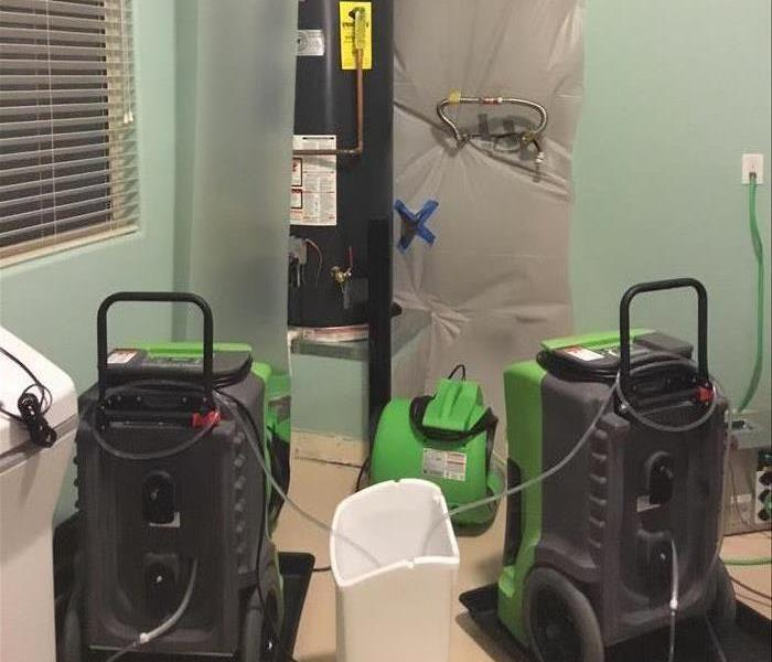 Secured room with three green air movers.