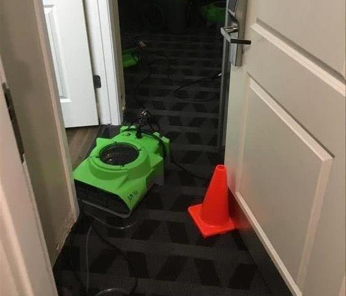 Green air movers on black carpet.